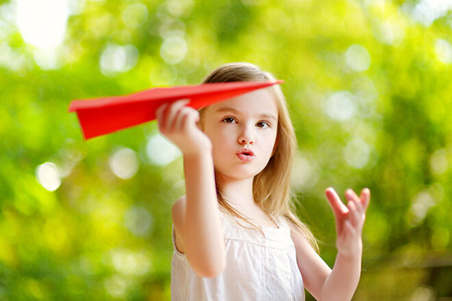 Little girl flying a paper plane