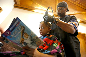 Iowa Barbar Courtney Holmes gives kids free haircuts if they read to him.