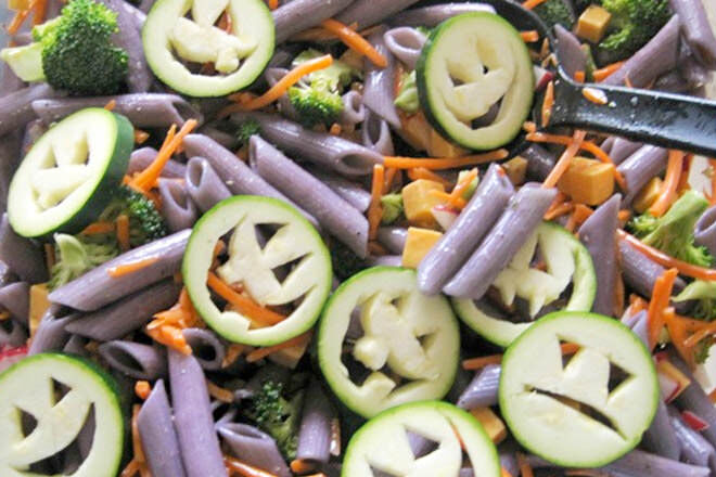 Zucchini zombie faces and a drop of food colouring in the cooking water will have the kids all spooked out over this Halloween pasta salad.