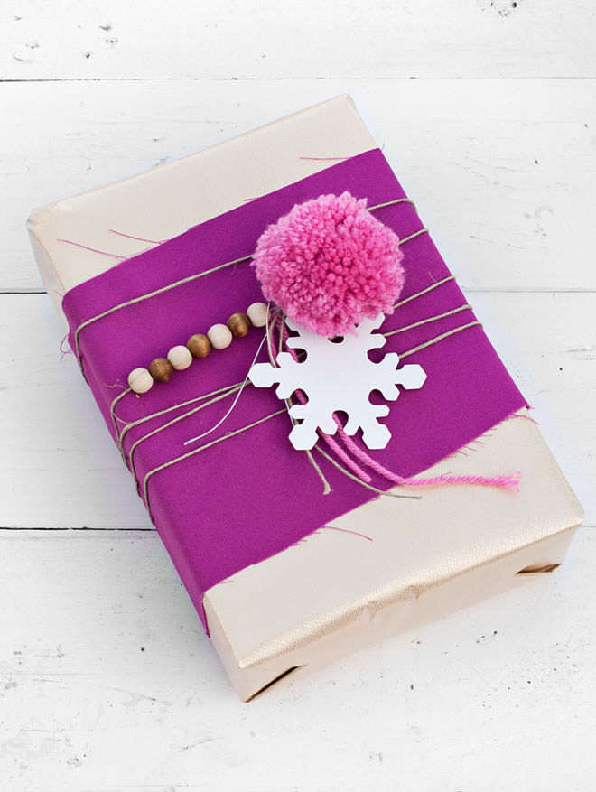 Gift wrapping with pom poms, string and fabric scraps
