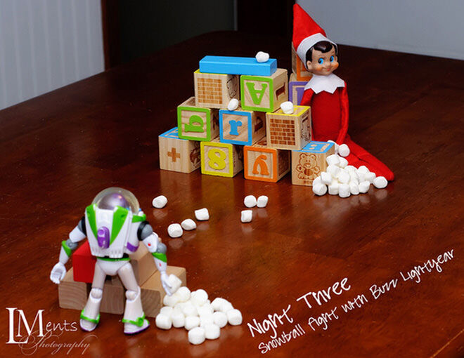 Elf on the Shelf and Buzz Lightyear have a snowball fight