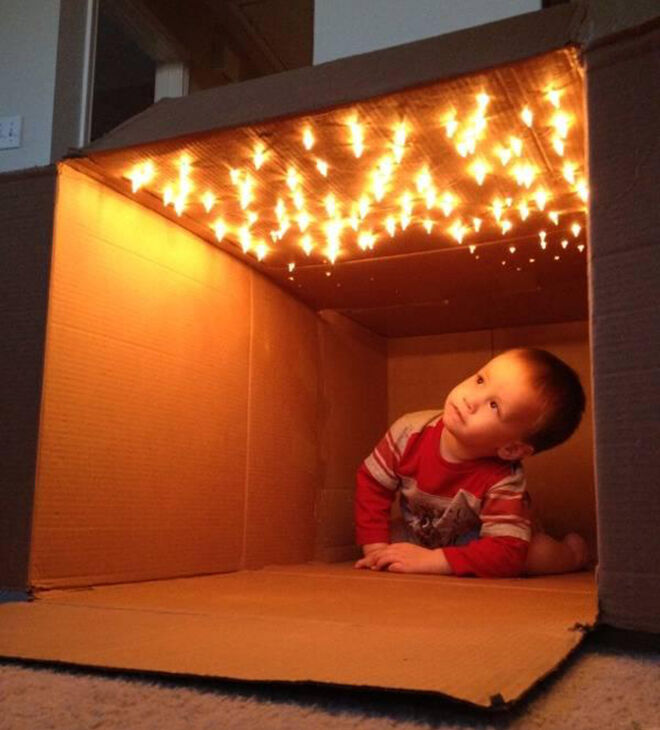 Cardboard fort with fairy lights.