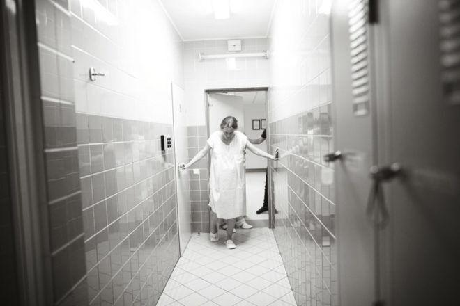 Pregnant walking in hospital corridor B+W