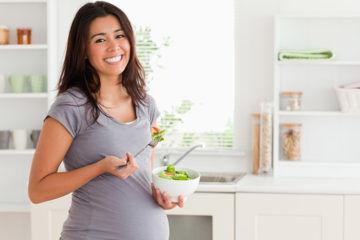 Happy pregnant women eating salad
