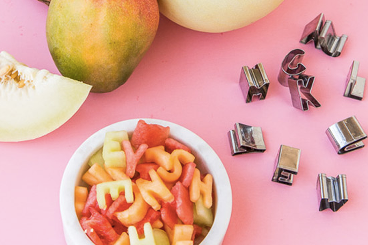 Cutting fruit in alphabet shapes with cookie cutters