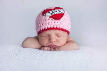 "Newborn Baby Girl Wearing a ""Love"" Hat"