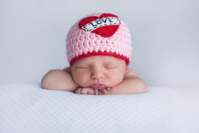 "Newborn Baby Girl Wearing a ""Love"" Hat"