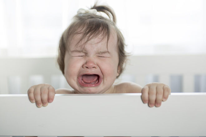 upset toddler in cot
