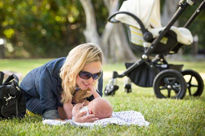 Mum and newborn baby in the park with a pram