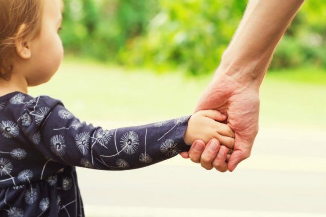 toddler holding hands with parent
