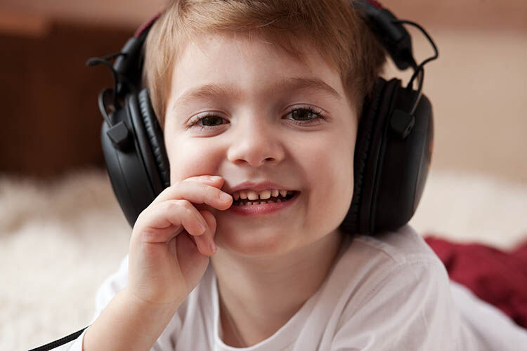 child listening to music through headphones Kinderling
