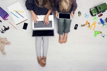 children using laptop and tablets ignoring their toys