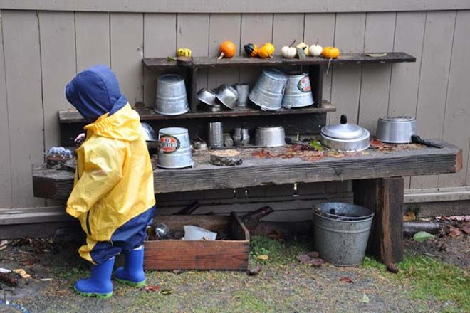 outdoor mud kitchen toddler play wearing gumboots