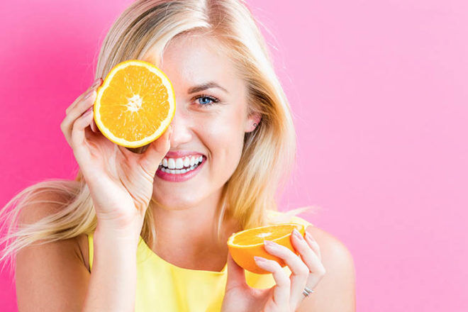 foods that boost fertility girl holding oranges