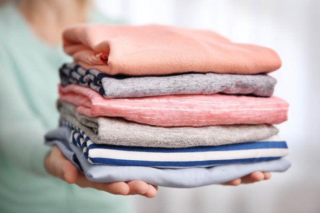 mum holding pile of clean washing