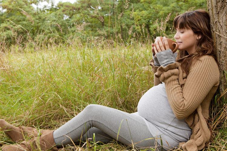 Pregnant woman drinking tea outside