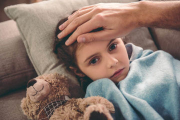 Sick girl in bed with teddy