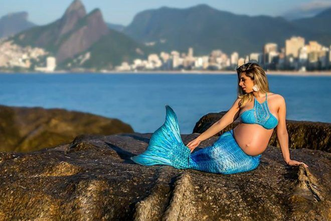 Pregnant mother as mermaid with city in background