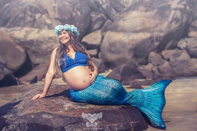 Pregnant mother dressed as mermaid on rock at beach