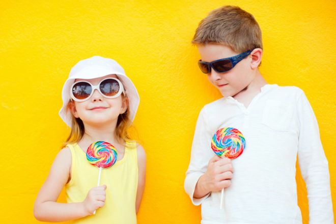 Kids with lolly pops on yellow background