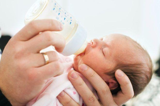 dad feeding sleeping baby a bottle