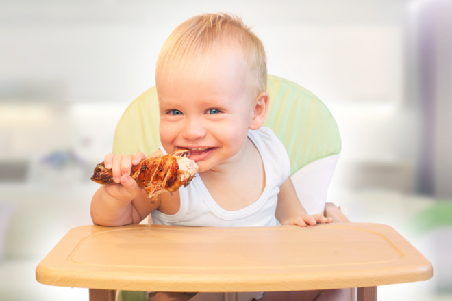 Toddlers eating chicken drumstick with hands