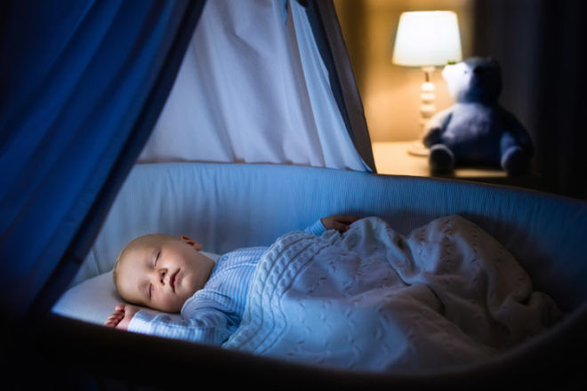 Sleeping Baby in a cot at night si