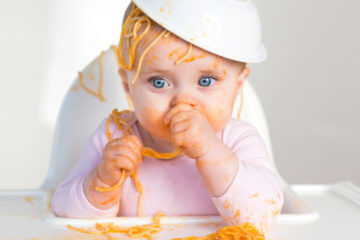Little girl playing with food spaghetti