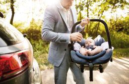 Man carrying baby in car capsule