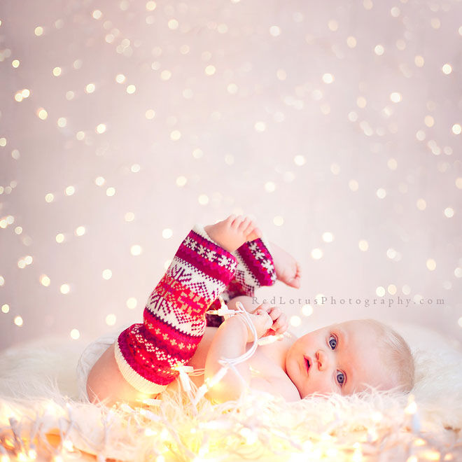 Baby's first Christmas photo, dressed in leg warmers with fairy lights