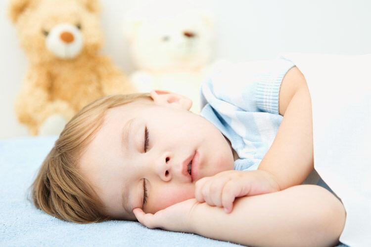 Sleeping baby boy and teddy bear
