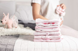 Pregnant woman folding clean baby clothes