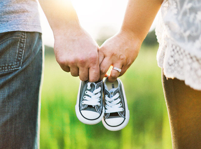 Holding baby shoes pregnancy announcement
