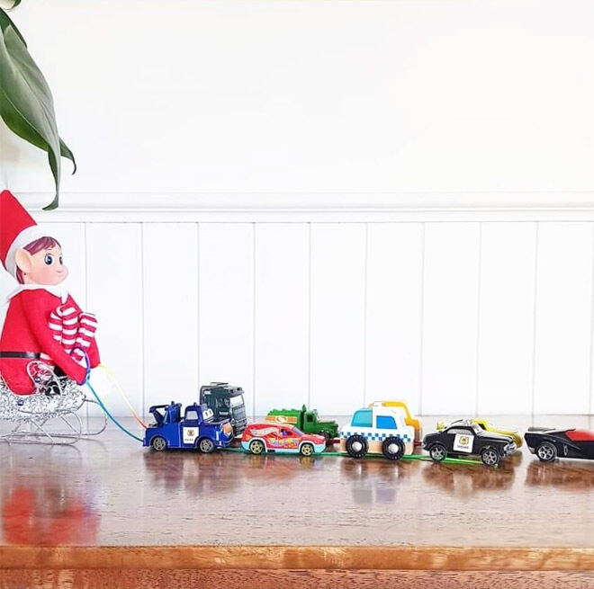 Elf on the Shelf pulling toy cars