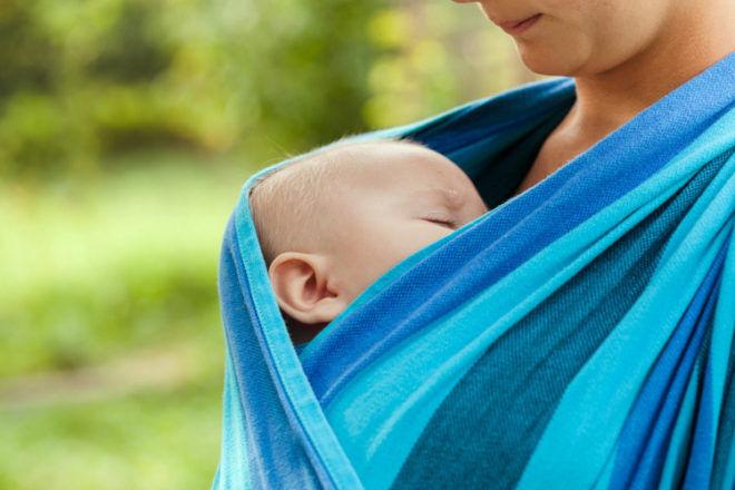 sleeping baby in sling carrier